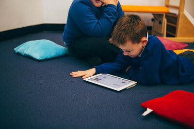 child using iPad on floor in classroom