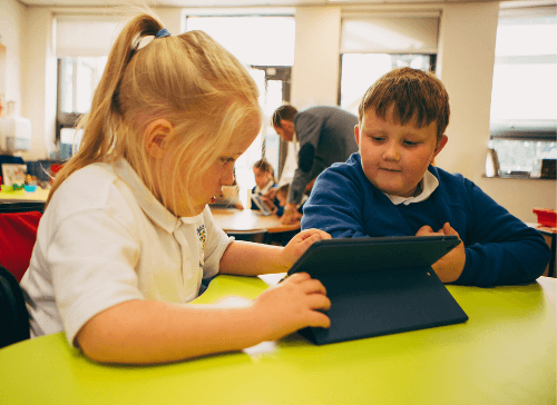 boy and girl using iPad at table in school classroom
