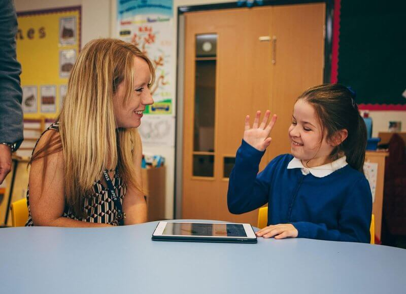 girl using sign language with teacher in classroom