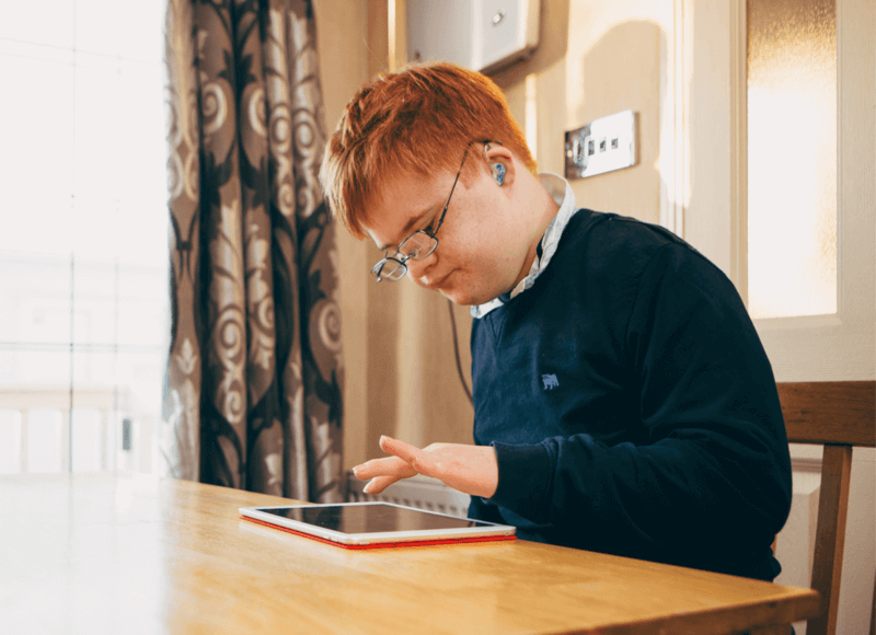 boy using iPad at table at home